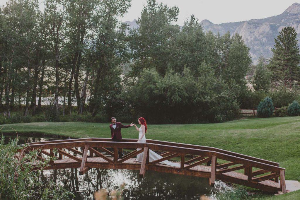 Bride and Groom on a bridge , wedding portraits in Estes Colorado
