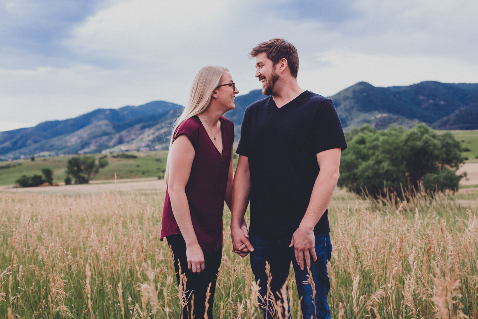 Couple laughing in a field for a Colorado Engagement Session